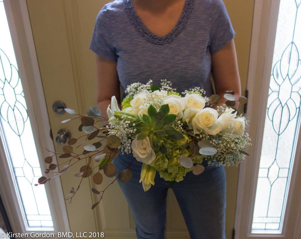 "Simple white and green bridal bouquet - 30"" wide  Classic roses paired with lilies, succulents, and silver dollar eucalyptus for asymmetrical interest."