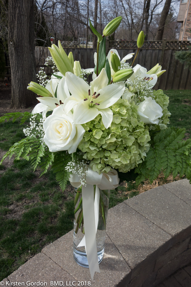"Simple white & green tall arrangement - 48"" Height  Designed to encourage guests at the table to converse. Features lilies, hydrangea, and roses. Can be done in many color schemes."