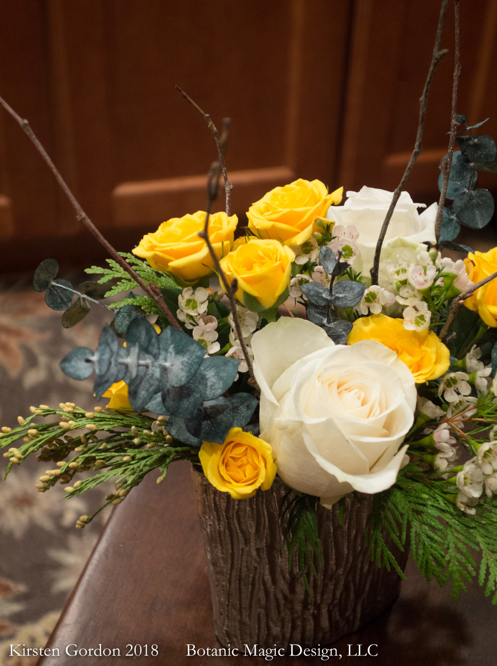 "Petite winter woodland bouquet - 12"" height  Evergreens and eucalyptus join roses in this colorful combo."