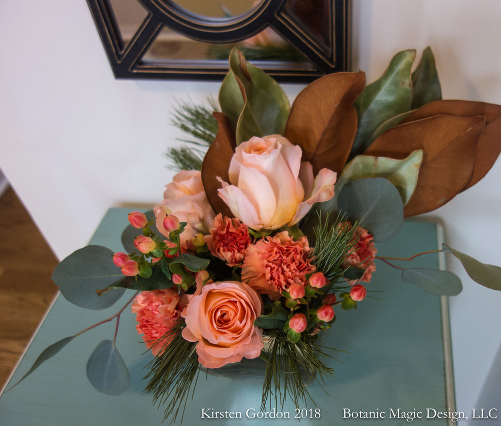 "Modern winter roses and greens - 14"" height  A January party called for peach, we brought in magnolia leaf, eucalyptus and fir to play up the season."