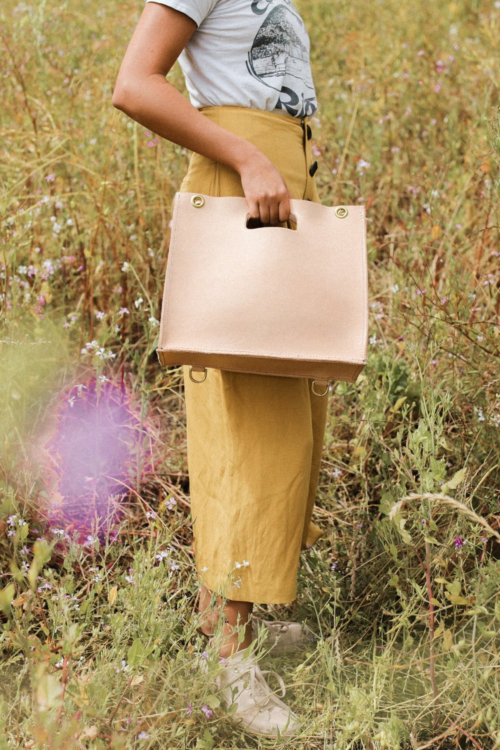 Model holds a new veg-tan Petite Tote. The leather starts off a very light blush or cream color.