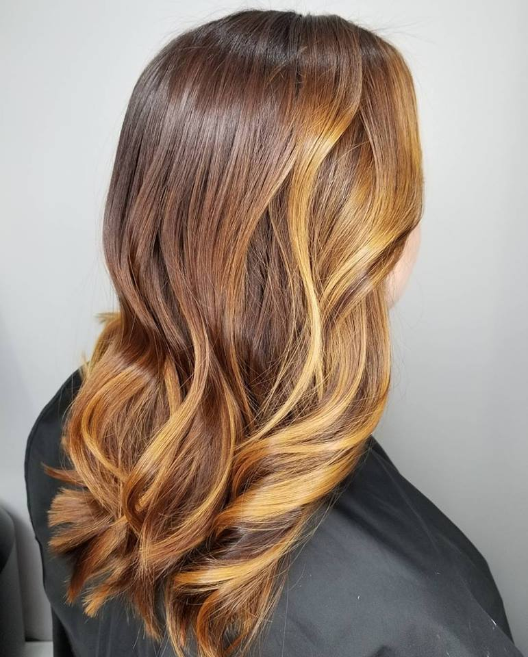 This would be considered a Balayage Ombre.  (Ombre is a transition from dark to light.)  I did this with an all over color and balayaged in low lights to give her hair more dimension.  Yet, leaving her a sunkissed look around her face.