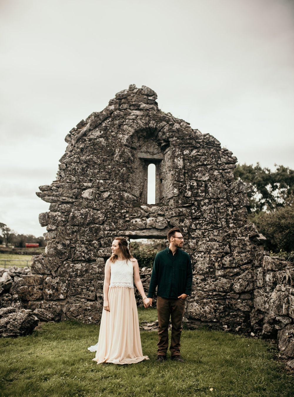 Husband and Wife holding hands during Vow Renewal in Ireland at an ancient ruins.