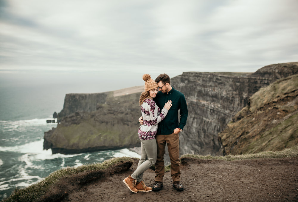 Husband and Wife snuggle during anniversary session on the Cliffs of Moher in Ireland