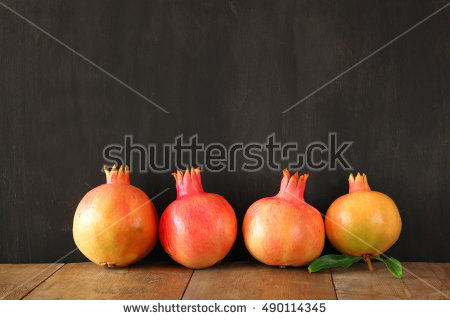 stock-photo-rosh-hashanah-jewesh-new-year-holiday-concept-pomegranate-over-wooden-black-background-490114345.jpg
