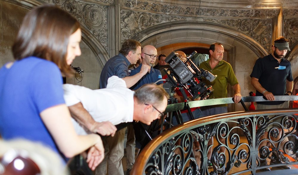 "The crew observing Genevive during the filming of the stairway scene, in Biltmore Estate during ""Serafina and the Black Cloak."""