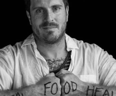 "Seamus Mullen with the words ""Real Food Heals"" written across his arms"