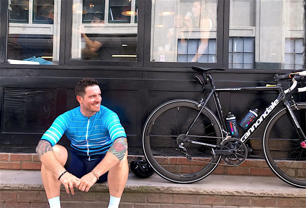 Seamus Mullen sits on a curb next to his bike