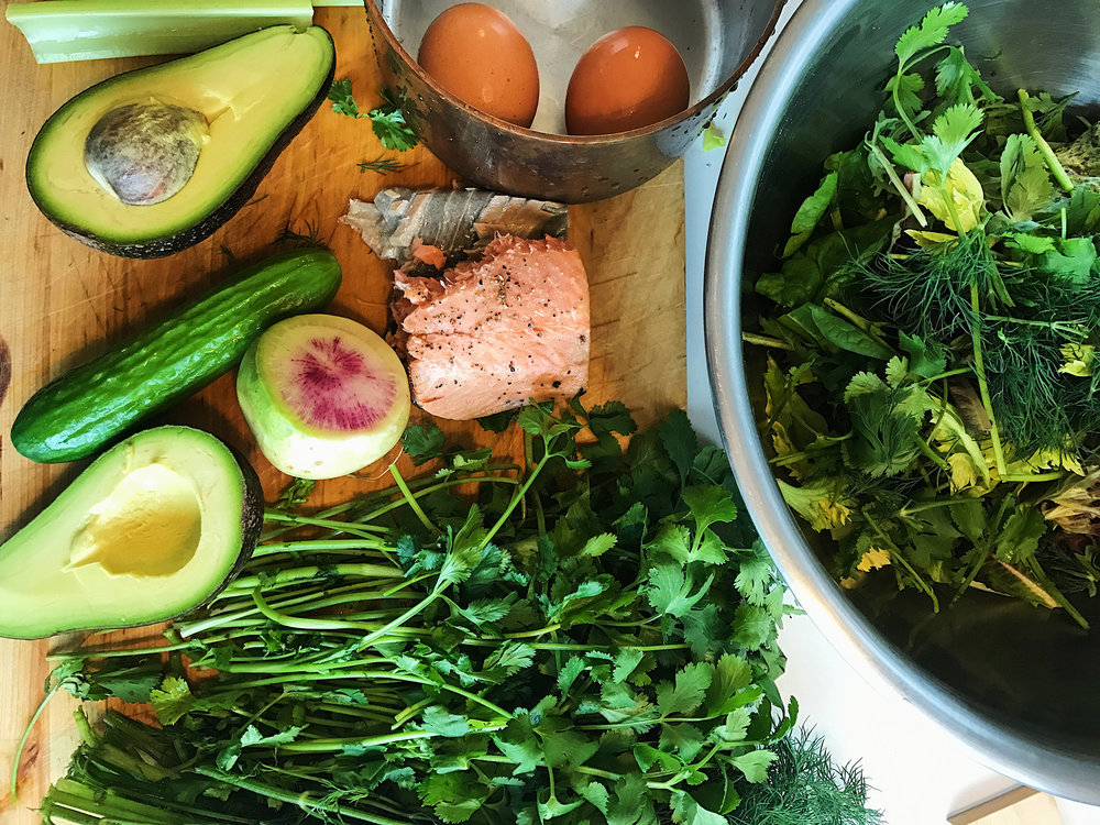 Kitchen counter filled with power foods avocado and salmon for a simple and healthy salad