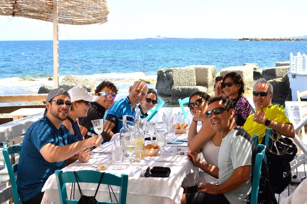Chef On Wheels Bike Tour guests toast at lunch with the sea in the background