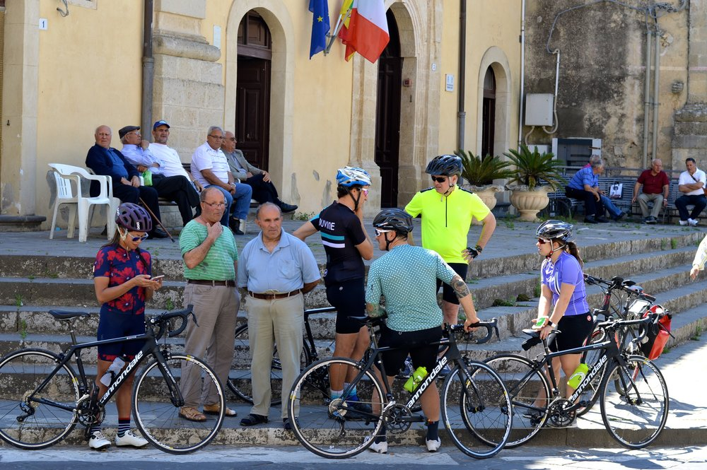 Cyclists in a town square in Sicily