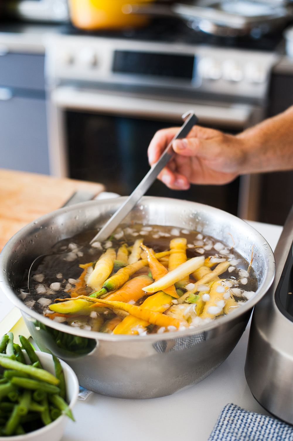 Organic yellow carrots soak in a metal bowl