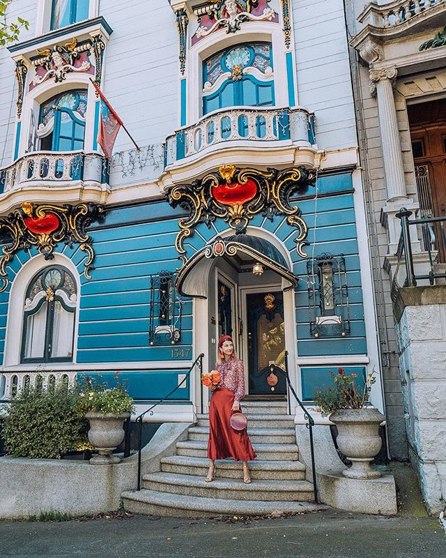 My favorite thing to do on a sunny day in San Francisco is going to a random area and zig-zagging all the streets in search of pretty Victorian houses ✨ :: This beauty is in the Alamo Square area and it's entrance is simply stunning! The yellow details are made with an actual gold leaf and the flag represents the family coat of arms 👸👏 :: Wearing red silk skirt by the talented @maggiewustudio :: #onlyinsf #mysf #sfblogger #alamosquare