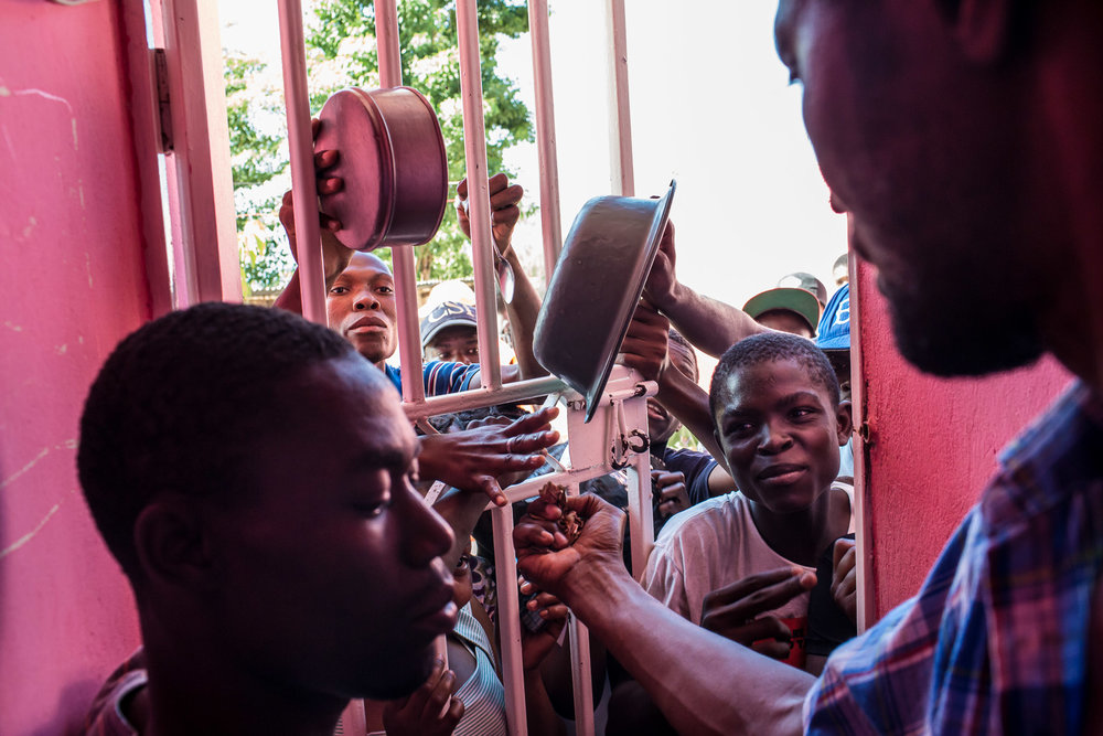 Owner Benoit Jean Wilfrid, right, collects money as people clamour for a plate of food at a restaurant in the Tapis Rouge neighborhood on Monday, December 22, 2014 in Port-au-Prince, Haiti. The restaurant was initially funded as a government program, and is required to serve meals that cost the equivalent of less than 25 cents US, which both provides cheap food for residents and a local business for entrepreneurs.