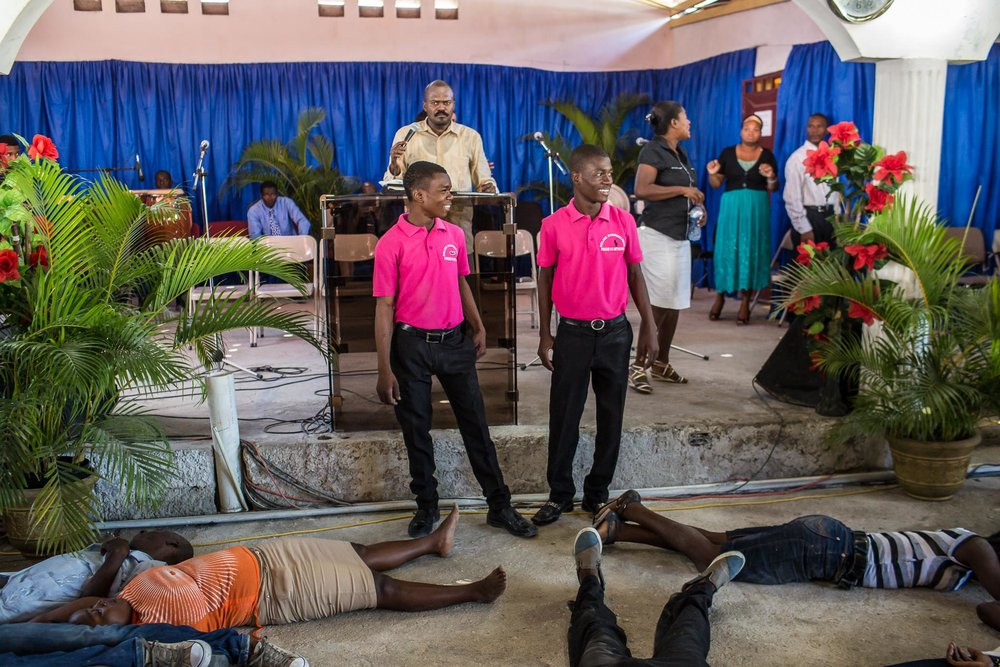 Ushers look over worshipers who have been overcome with religious fervor at L'Eglise Evangelique Piscine de Bethesda, the church of televangelist Marcorel Zidor, on Saturday, December 20, 2014 in Port-au-Prince, Haiti. Pastor Zidor attracts a large audience with his emotional services and miracle medical cures of dubious theraputic value.