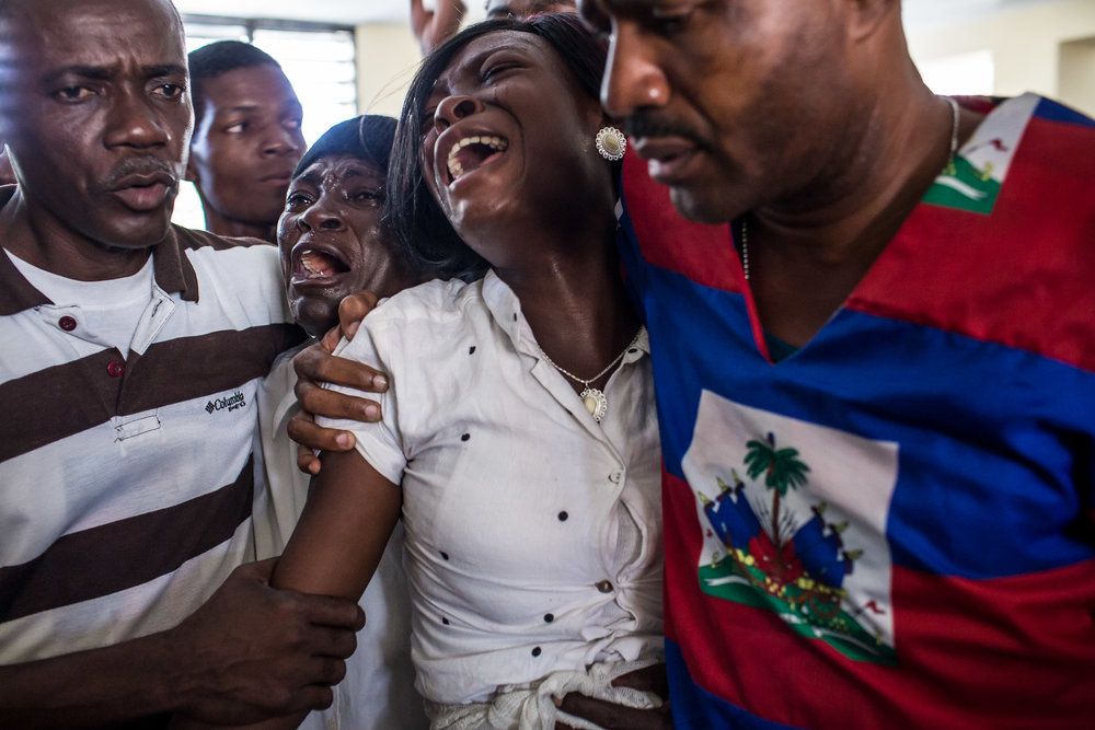 Claudiani Fonrose, third from left, and Bertha Nicolas, 20, second from right, grieve at the funeral of Jolin Nicolas, 19, on Monday, December 22, 2014 in Port-au-Prince, Haiti. Jolin Nicolas, their son and brother, respectively, was killed by police while participating in anti-government protests on December 13.