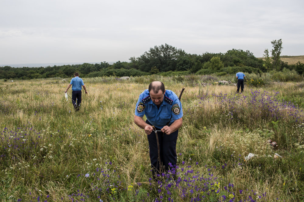 A Ukrainian Emergencies Ministry worker ties a white ribbon to a stake to mark human remains found in a field after a commercial passenger plane was shot from the sky by a missile the previous day on July 18, 2014 in Grabovo, Ukraine. Malaysia Airlines flight MH17 travelling from Amsterdam to Kuala Lumpur has crashed on the Ukraine/Russia border near the town of Shaktersk. The Boeing 777 was carrying 298 people.