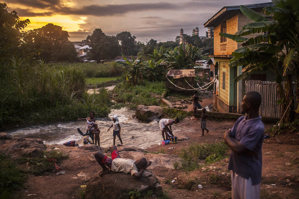 Residents of the town of Kailahun gather along a river at dusk on Tuesday, August 19, 2014. At the time, Kailahun district, in eastern Sierra Leone, was the most heavily affected by the ongoing Ebola outbreak, which originated across the nearby border with Guinea. (Pete Muller/Prime for the Washington Post)