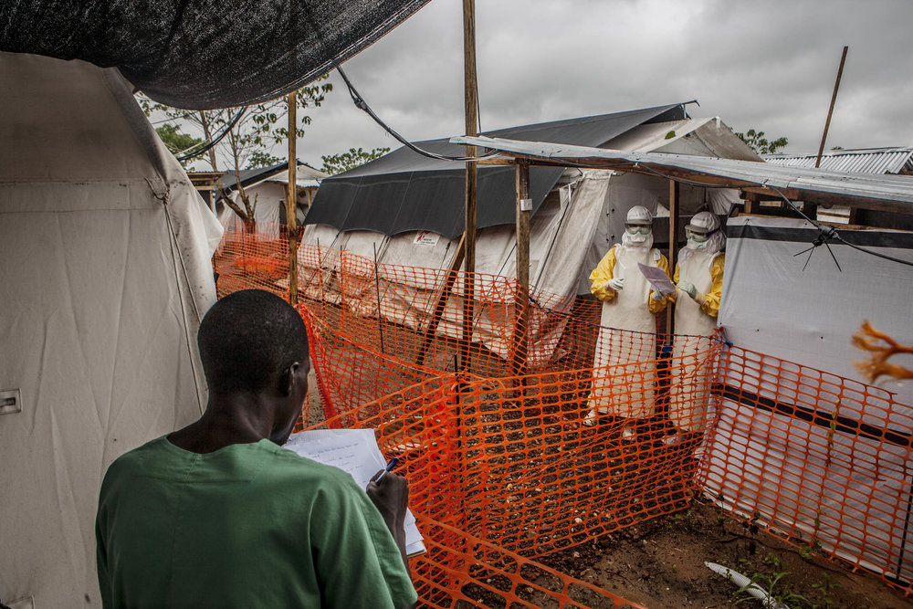 "Doctors Without Borders medical staff discuss patient status across an established safety cordon in an Ebola treatment center in Kailahun, Sierra Leone on Sunday, August 17, 2014. Those in masks stand in the ""high risk"" zone where highly contagious Ebola victims receive treatment. (Pete Muller/Prime for the Washington Post)"