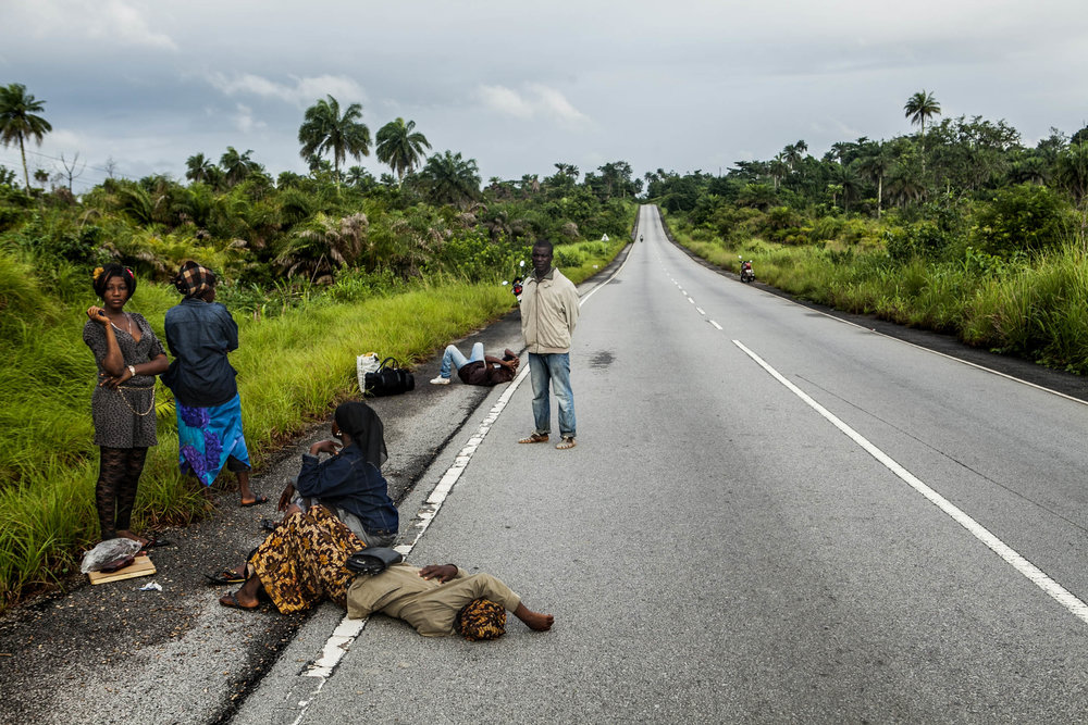 People who were denied passage at a checkpoint outside of Kenema wait on the roadside on Friday, August 22, 2014. Only those in possession of a government issued permit are allowed to cross Ebola quarantine checkpoints. (Pete Muller/Prime for the Washington Post)