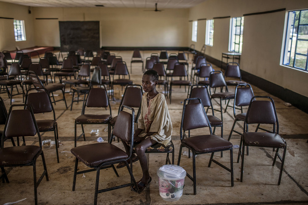 Molai Kamara, approximately 12 years old, sits alone following a discharge ceremony for Ebola survivors at the Hastings Ebola Treatment Center in Hastings, Sierra Leone on Saturday, November 29, 2014. While excitement buzzed outside as the other 55 survivors received food supplies and boarded buses to return home, Molai sat alone, still sick with other ailments and with nowhere to go. According to doctors at Hastings, Molai lost his entire family to the Ebola virus. He was unconscious for the first two weeks of his time in the Hastings treatment center. While he eventually tested negative for Ebola, he continues to suffer from ulcers and has great difficulty walking. While fellow survivors returned home, Molai was transferred to a nearby hospital where he will receive additional care while administrators search for caregivers. (Pete Muller/ Prime for National Geographic)