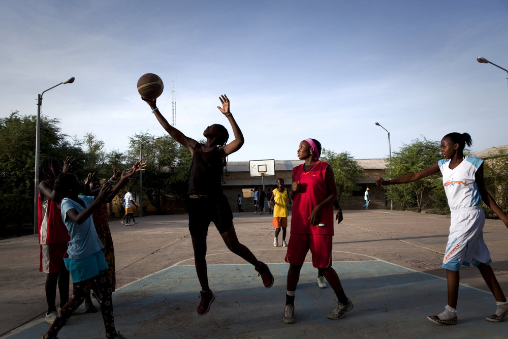 "TIMBUKTU, Mali. OCTOBER 2013. Girls play basketball in downtown Timbuktu, Mali, as part of the Academie de Basket coached by El Hadj Adjanga, a 54-year-old local butcher.  ""I can tell you this..the first week after liberation -- as soon as they could do it -- the kids were back here playing,"" he said. In the early days of the Jihadist occupation of Timbuktu, these girls would cover up in the face-concealing niqabs and full-length burkas as demanded, wear it while walking to the courts, and then just take them off and play. Eventually, the situation grew too dangerous to even stay in Timbuktu, and most of the young women fled for Bamako, returning just recently. 
