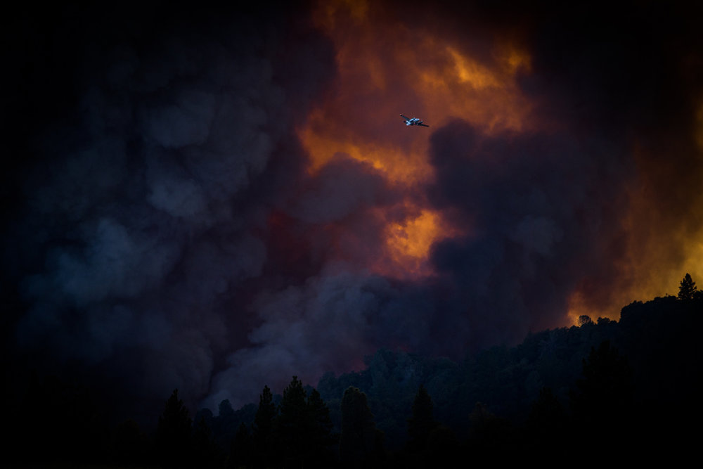 A spotter plane flies past the Sand Fire as it burns near Plymouth, California, July 26, 2014. 