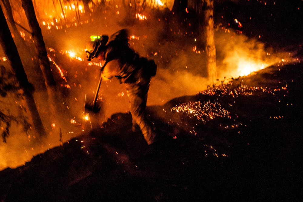 Firefighter Dave Beck rakes embers away from a road on the Rim Fire near Buck Meadows, California, August 22, 2013. The fire burned 257,314 acres in and around Yosemite National Park, and is the biggest wildfire on record in the Sierra Nevada.