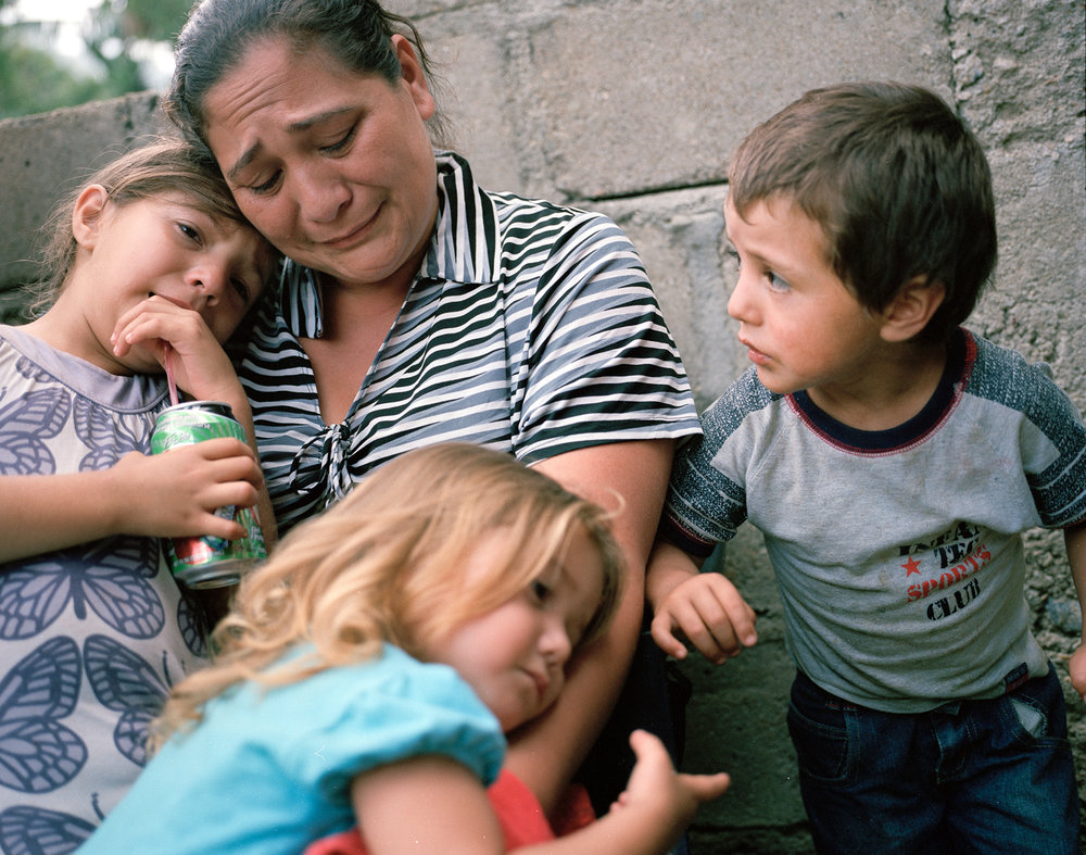 Lizeth Cerros mourns her murdered husband, Darwin Franco, with her children, later she received another death threat. Franco was a community organizer.