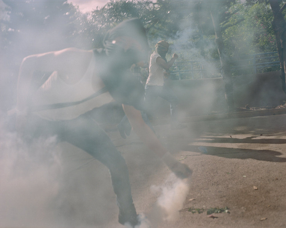 University students throw teargas bombs back at police during an anti fraud protest in Tegucigalpa.