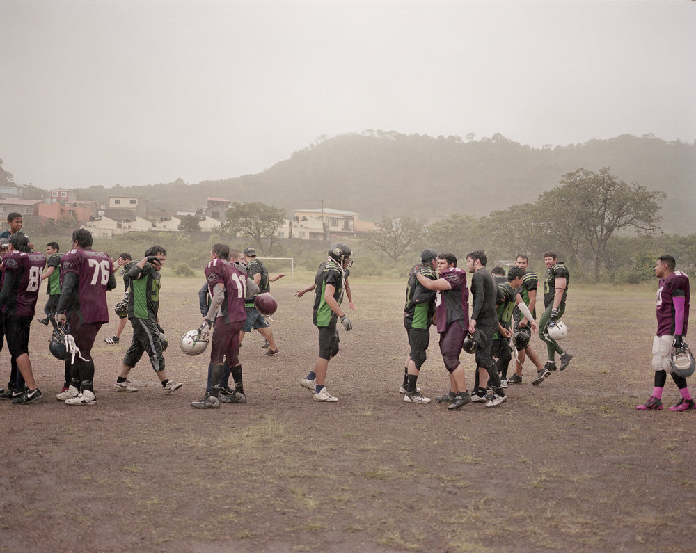 Two teams from the Honduran National American Football League congratulate each other in the rain after a game.