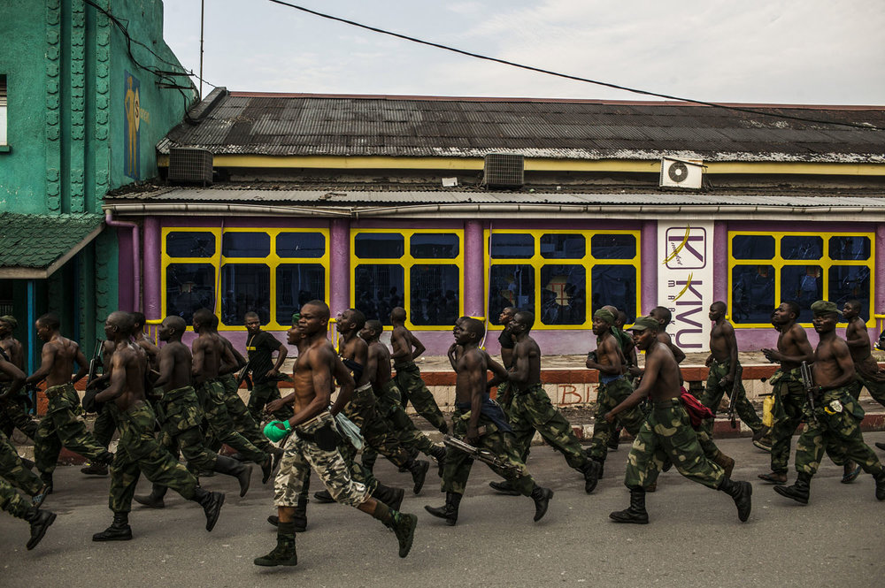 Congolese soldiers jog through downtown Goma on a Saturday morning. The weekly jogs are a relatively new feature, designed to inspire confidence and patriotism in the city's residents.