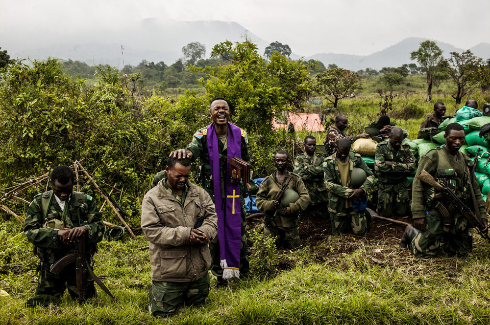 A Congolese military chaplain prays with soldiers at the frontline in Kibumba, outside Goma. This position is the furthest advance point of the military. Members of the M-23 rebel group are within shouting distance.