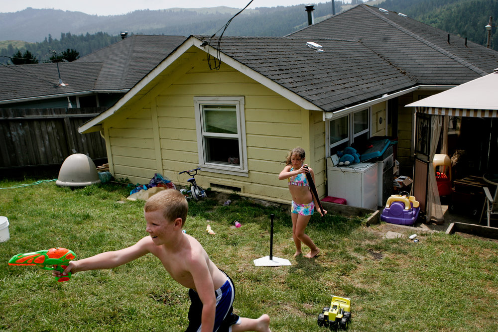 From left, Sheldon Eilers, 10, and Alexa Taylor play in the backyard of a Scotia, CA home on Tuesday, June 27, 2006. The town of Scotia in Northern California is a company town owned by the Pacific Lumber Company (PALCO), but that will change as the company will begin to sell the town.