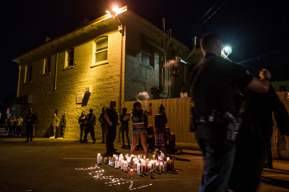 Members of Stockton's Community Response Team question mourners at the site of a memorial for five people shot the night before in Stockton, California, September 18, 2013. Facing stark and rising homicide rates, the California cities Oakland and Stockton are taking a second chance at a novel method of disrupting street gangs, called Ceasefire, in which the police use social-analytics software to map out connections between a cityís most violent gang members, using the data to make targeted and coordinated arrests.