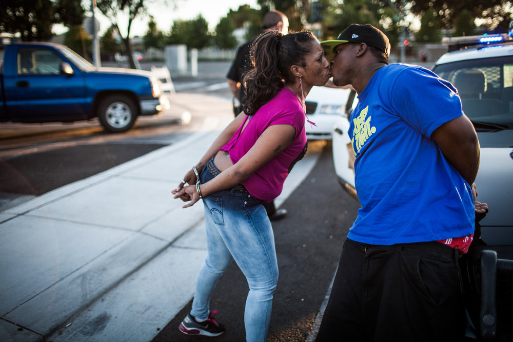 A couple kisses as they're separated and arrested after a handgun and drugs are found in their car during a traffic stop by the Community Response Team in Stockton, California September 18, 2013 which targets violent gangs. The officer found a handgun and heroin in the car. Facing stark and rising homicide rates, the California cities Oakland and Stockton are taking a second chance at a novel method of disrupting street gangs, called Ceasefire, in which the police use social-analytics software to map out connections between a cityís most violent gang members, using the data to make targeted and coordinated arrests.