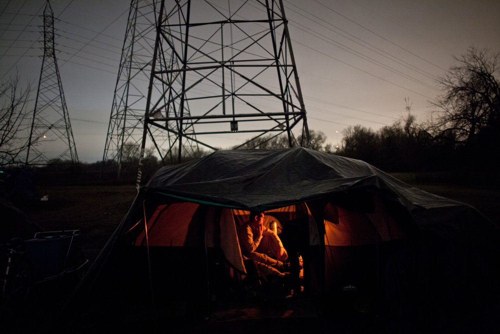 Campers stay warm in a tent heated by a propane burner at the SafeGround homeless tent camp in Sacramento, California.