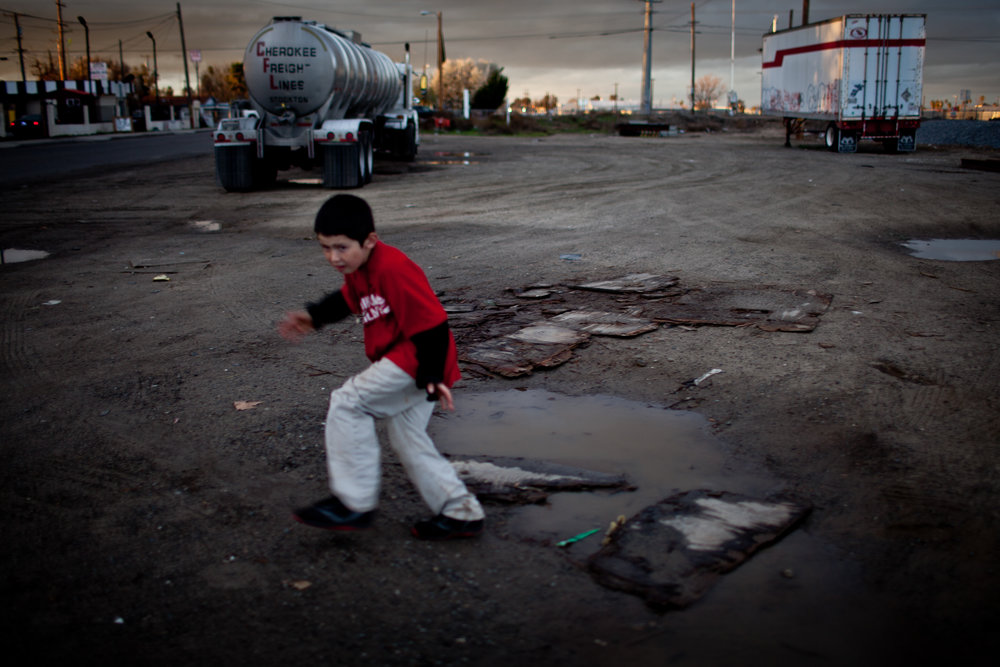 Ten-year-old Benito Tirjeron jumps over a puddle on the edge of the Parklawn neighborhood in Modesto, California. Across California there are hundreds of unincorporated communities like Parklawn. While a few are some of the state's richest areas; most lack sewer systems, clean drinking water, sidewalks, street lights, and storm drains. Populated by poor, working class Latinos, they're neglected by local government and lack the resources to install the most basic infrastructure that city residents rely on.