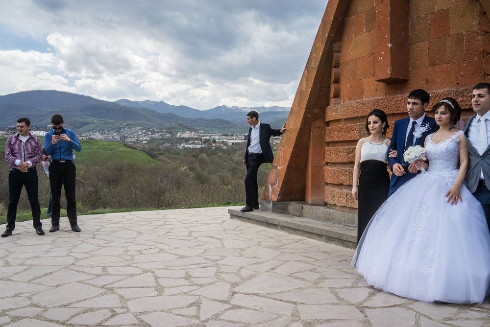 Groom Davit Simonyan, 24, and bride Shogher Hovsepyan, 25, take photos with family and friends at the Tatik Papik monument, a popular symbol of Nagorno-Karabakh, on April 18, 2015 in Stepanakert, Nagorno-Karabakh. Since signing a ceasefire in a war with Azerbaijan in 1994, Nagorno-Karabakh, officially part of Azerbaijan, has functioned as a self-declared independent republic and de facto part of Armenia, with hostilities along the line of contact between Nagorno-Karabakh and Azerbaijan occasionally flaring up and causing casualties.