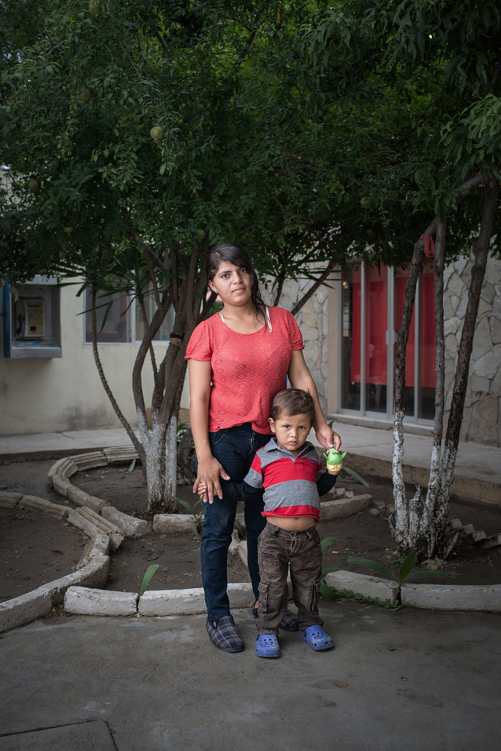 "Portrait of Diana Marisol (19 years old) and her son Denis Jose (3 years old) at ""Casa del Migrante Frontera Digna"" created by priest Jose Guadalupe Valdes Alvarado. Diana left her homecountry Honduras due to the violent situation her country is facing; ""I didn't want that future for my kid"", she said. ""Casa del Migrante Frontera Digna"" was created to provide lodging for migrants from different countries who arrive after long journeys that last several months to cross into the United States. Immigrants can spend three nights in the shelter where they are offered beds, food, hygiene items and a space to regain strength. Piedras Negras, Coahuila, Mexico. June 21st, 2018. Photographer: Luján Agusti."