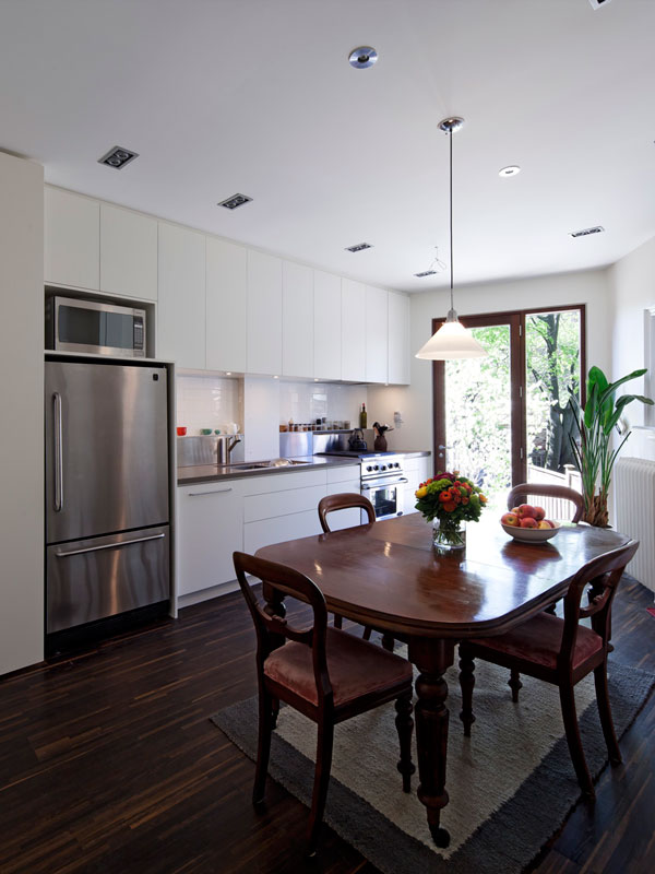White Cabinets with Dark Engineered Wood Floor and Mahogany Doors to Backyard Deck Beyond