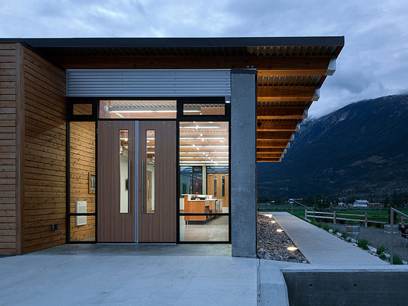 As visitors open the oversize wood doors to enter, they step into a welcoming tasting room with a stunning view overlooking the Fraser River Valley, the mountains beyond and the vineyard below.