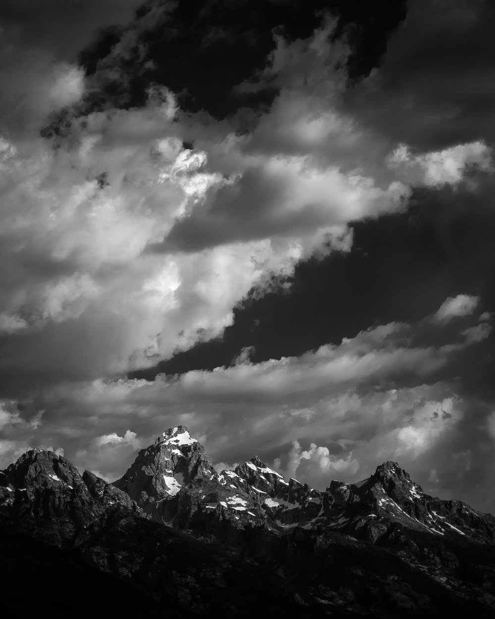 A black and white photograph by fine artist Cody Schultz, this high-contrast photograph of the Grand Teton mountain range is one of few vertical images made by the artist. The glaciers on the mountaintops glisten a pure white, contrasted by the black and deep grays of the rest of the mountain. The sky, full of clouds, helps to create drama within the scene.