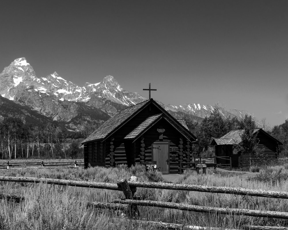 A black and white photograph taken by fine artist Cody Schultz while on family vacation out to Wyoming. This photograph features a chapel/church in front of the Grand Teton mountain range near Jackson, Wyoming. A fence made of long, thin logs sits in the foreground, pointing up towards the church, which points up to the mountains, and the blank, gray sky.