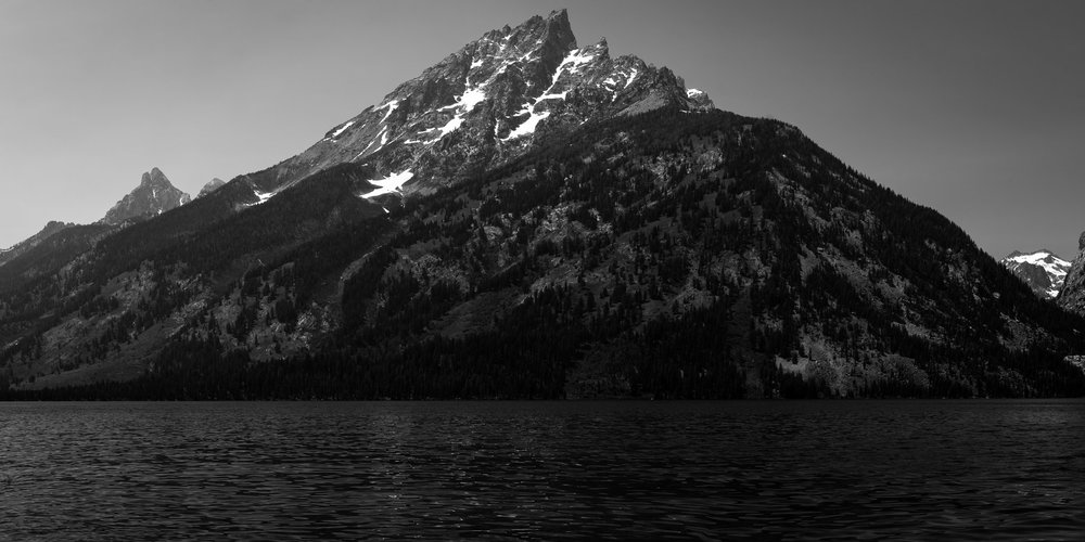 A black and white photograph by fine artist Cody Schultz, Standing Tall is a panoramic view of a mountain above a lake. Everything in this photograph - especially when printed - shimmers; from the highlights in the water to the bright white glaciers on the mountaintops, every inch of this photograph shines like no other.