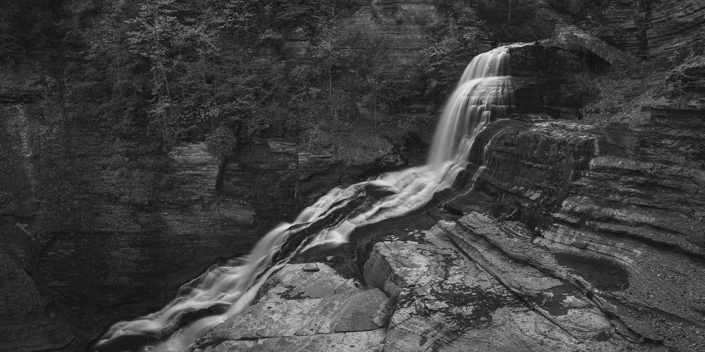 A black and white photograph by fine artist Cody Schultz, this piece was created while exploring a handful of waterfalls in New York state during a camping trip. Another panoramic piece, this photograph shows Lucifer Falls as it rushes from corner to corner of the frame, standing out just enough from the rest of the scene which ranges in from a plain gray to a deep black tone.