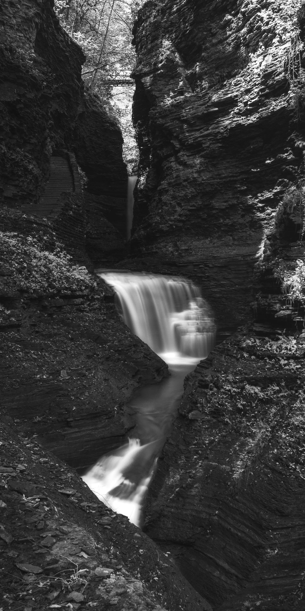 A black and white photograph by fine artist Cody Schultz, Watkins Glen is a vertical panorama, one of the first by the artist. The scene shows a grouping of waterfalls, hidden by the rock walls that frame it on either side. Near the top of the frame stands a bridge that connects either side of the walls; toward the left of the frame is a rock staircase with no sign of people, a rare sight for such a popular destination.