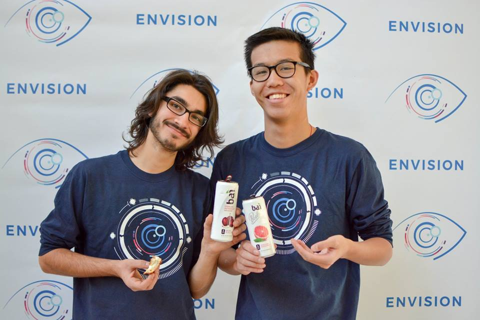 Envision Conference team members Taylor Kulp-McDowall and Gerry Wan show off their free drinks during the conference.