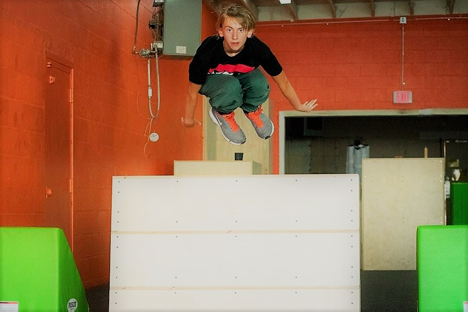 Parkour 101 - This class is aimed at beginner to intermediate level athletes ages 14 and up. Students will gain the skills and experience to plan and execute traversing obstacles using parkour specific movements. Students will learn movements from various categories including rolls, jumps, vaults, wall movements, and movements on bars/ropes. Rolls include shoulder rolls, reverse rolls and rolling out of other movements. Jumping topics include jumps at different elevations, precision jumps, and different stride variations. Vaults include the safety vault, speed vault, kong vault, and more. Wall movements include wall runs, wall pop, wall to cat climbs, 270 wall runs, tic-tacs, and wall flips and variations. Bars/ropes include pullovers, laches, laches to precision, and rope climbs/swings. Time trials and games like HORSE will test their skills.