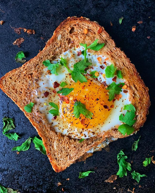 Currently nursing a sinus infection, but trying to stay sunny side up with these eggs in baskets 🍳 Cut a hole in the center of a piece of bread, and set the cut piece aside (it's great for dipping into the yolk). Butter and toast both sides of the bread on a griddle until golden brown (toast the cut piece, too). Crack an egg into the hole, reduce heat, and cover the pan, cooking until the egg is just set but the yolk is still runny. Sprinkle with sea salt, black pepper, and herbs. ✨ #afsanaliza